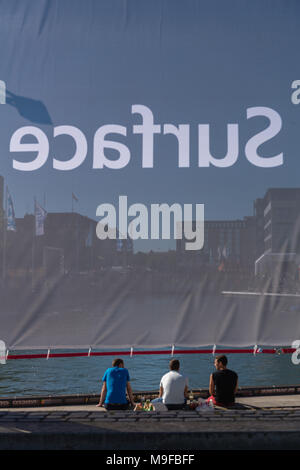 Three young men sitting at the Bootshafen, taken through a net with the inscription '(Microsoft) Surface', world´s biggest sailing event 'Kiel Week', - Stock Photo
