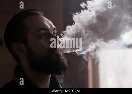 Man with Beard and Mustages Vaping an Electronic Cigarette. Vaper Hipster Smoke Vaporizer and Exhals Smoke Cloud. - Stock Photo