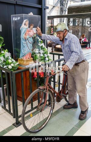 Buenos Aires Argentina Estacion Retiro train station interior Catholic religion religious display Virgin Mary statue man touching case senior bicycle - Stock Photo