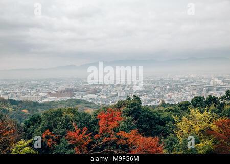 Kyoto city and autumn maple view under cloudy sky at Fushimi Inari shrine in Kyoto, Japan - Stock Photo