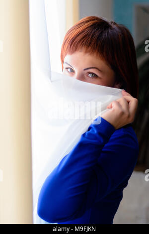 A beautiful woman in a blue dress is in the room near the window 2018 - Stock Photo