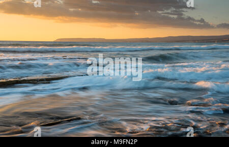 Rocky seashore seascape with wavy ocean and waves crashing on the rocks during a dramatic and beautiful sunset at Akrotiri coast  in Limassol, Cyprus - Stock Photo
