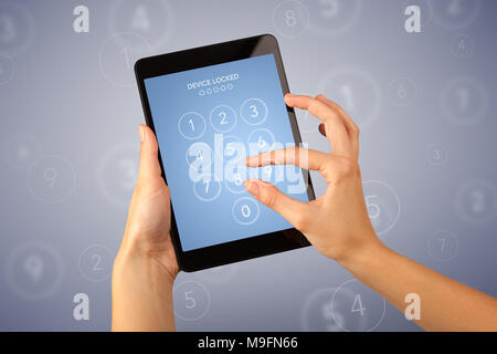 Female fingers touching tablet with locked device requiring passcode - Stock Photo