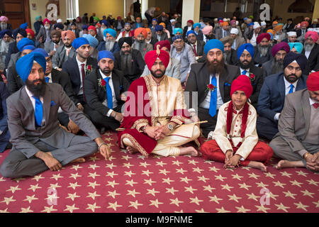 A groom seated with his brother at the beginning of a Sikh wedding ceremony in Richmond Hill, Queens New York. - Stock Photo