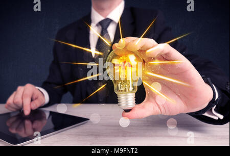 A male business person holding an electric light bulb in his hand with beam rays illustration concept. - Stock Photo