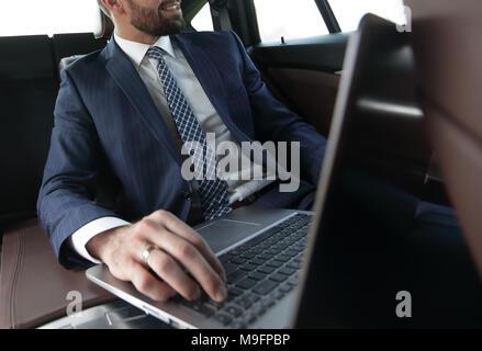 Confident businessman sitting in car - Stock Photo