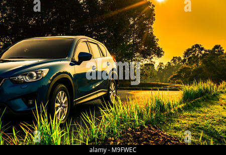 Blue compact SUV car with sport and modern design parked on concrete road at sunrise with orange sky. Environmentally friendly technology. Business su - Stock Photo