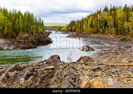 42,620.04772 Whirlpool Canyon, curving Laird River, big left bend in the river, tipped rocks, wide fast water, rocky shore edge, conifer trees forest - Stock Photo