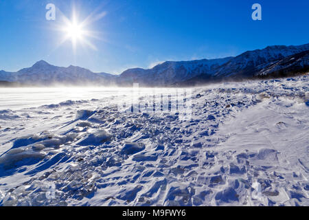 42,747.08303 snow swept Abraham Lake ice clumps shore, mountains in background, sun rays, sun blue sky, drifting snow - Stock Photo