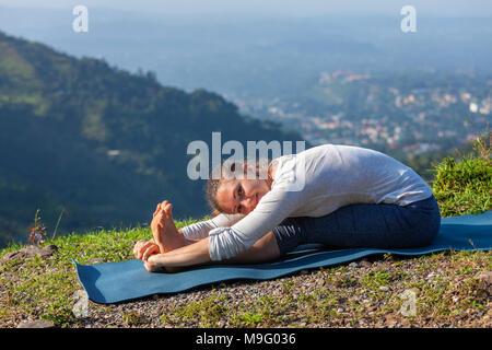 Woman doing yoga asana Paschimottanasana forward bend - Stock Photo