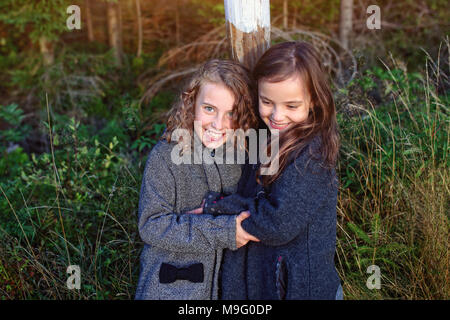 happy girlfriends cuddle and laugh - Stock Photo