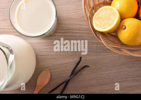 Glass of milk and jug on wooden bench in a rustic kitchen with lemons and cinnamon. Horizontal composition. Top view - Stock Photo