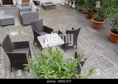 Grey garden furniture with flowers in pots on terrace of spacious hotel Vienna, Austria - Stock Photo