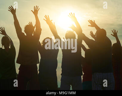 Fans at open air concert, back view. Open-air rave party. Raising hands up. - Stock Photo