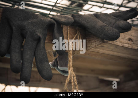 Close up of rubber gloves of a farmer lying in greenhouse. Hard work concept. Vintage style. - Stock Photo