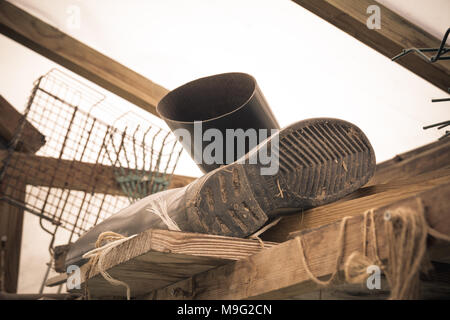 Rubber boots of a farmer lying in greenhouse. Tough work concept. Vintage style. - Stock Photo