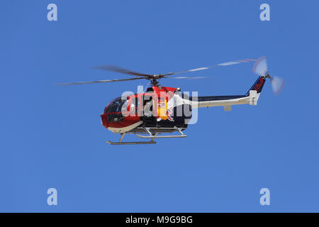 Lancaster, USA. 25th Mar, 2018. The Red Bull aerobatic helicopter is shown flying over the Los Angeles County Air Show, as a crew member waves to the crowd. Credit: Kilmer Media/Alamy Live News - Stock Photo