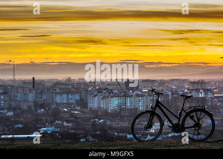 Modern sports city bicycle standing alone over night city background with many bright lights. View of orange sunset sky in Ivano Frankivsk city, Ukrai - Stock Photo