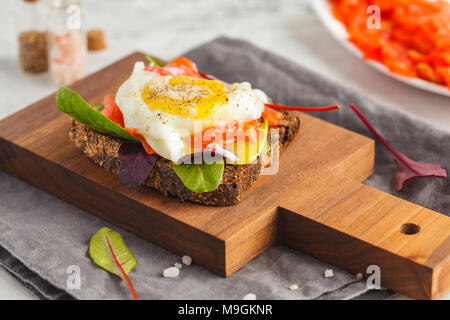 Fresh sandwich with egg poached, red fish on rye bread. Keto-balanced diet food. - Stock Photo