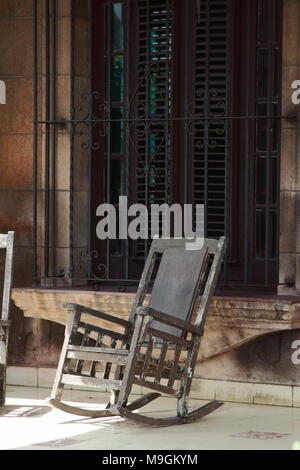 A rocking chair on a sunny porch in the center of Havana, Cuba. - Stock Photo