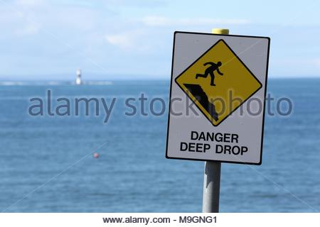 A yellow Danger deep drop sign warns people against going close to a steep cliff on the west coast of Ireland. - Stock Photo
