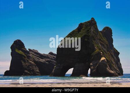 Huge rocks on Wharariki beach, New Zealand - Stock Photo