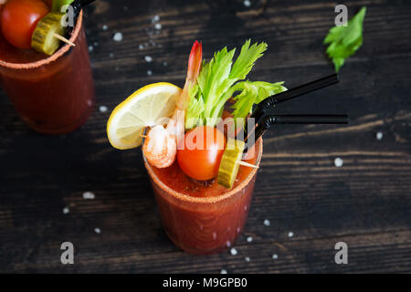 Bloody Mary Cocktail in glass with garnishes. Tomato Bloody Mary spicy drink on black background with copy space. - Stock Photo