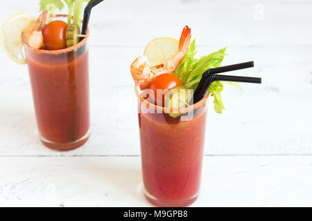 Bloody Mary Cocktail in glass with garnishes. Tomato Bloody Mary spicy drink on white background with copy space. - Stock Photo