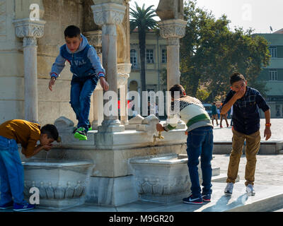 IZMIR, TURKEY - OCTOBER 04, 2014:  Young generation at the Clock Tower, Ottoman architecture of historic symbol of Izmir at the  Konak Square, built i - Stock Photo