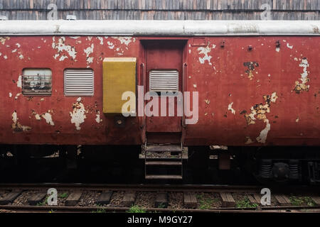 Old red railway carriage standing on station - Stock Photo