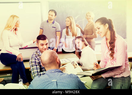 Teacher explaining interesting topic to curious students during a break in a classroom of university - Stock Photo