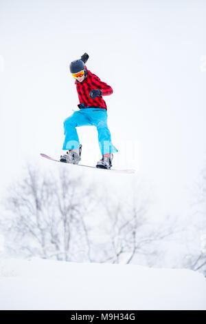 Image of sportive male snowboarder jumping on snowy hill - Stock Photo