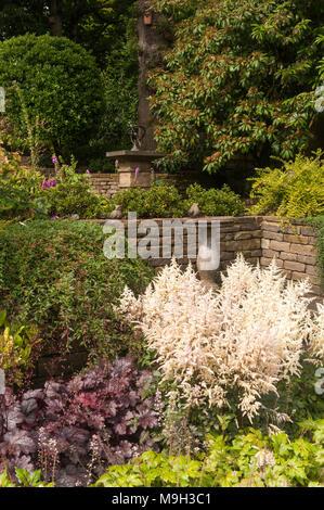 Small terraced area with stone sundial, bird bath, raised borders, shrubs & plants - beautiful, traditional, landscaped garden - Yorkshire, England. - Stock Photo