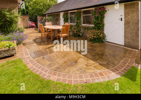 Designed & landscaped garden with curved paved patio, lawn, trellis screen, wooden table & chairs by garage of house - West Yorkshire, England, UK. - Stock Photo
