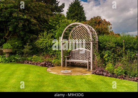 Wooden trellis seat arbour, mosaic art, lawn & summer border plants in beautiful, traditional, designed, landscaped garden - West Yorkshire, England. - Stock Photo