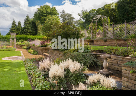 Terracing, flowering plants on border, lawn, stone walls, wooden trellis arch & arbour - beautiful, designed, landscaped, garden - Yorkshire, England. - Stock Photo