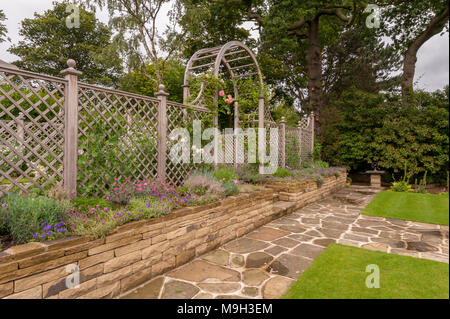 Path, flowering plants on border, lawn, stone wall, wooden trellis arch & screen - beautiful, designed, landscaped, garden - West Yorkshire, England. - Stock Photo