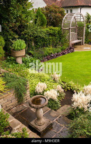 Wooden trellis seat arbour, bird bath, lawn & summer border plants in beautiful, traditional, designed, landscaped garden - West Yorkshire, England. - Stock Photo