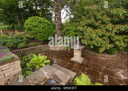 Small shady paved terraced area with stone sundial, raised border, shrubs & plants - beautiful, traditional, landscaped garden - Yorkshire, England. - Stock Photo