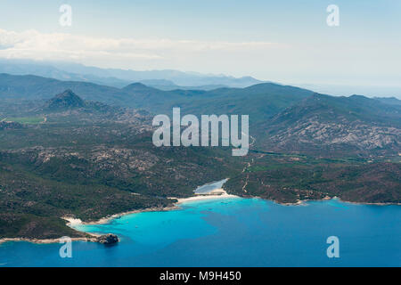 Aerial image of turquoise blue waters at the Corsican coastline West of Saint-Florent showing Punta Cavallata and Plage du Lotu and hills of the inlan - Stock Photo