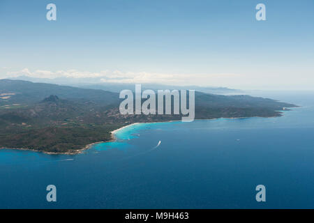 Aerial image of Corsica turquoise coastlinge showing Pointe de Curza and Punta di Furmiguli and Plage de Saleccia with private yachts - Stock Photo