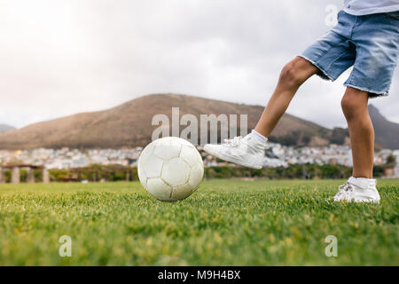 Close up of boy kicking a football in a playground. Low angle view of a boy playing football in a playfield. - Stock Photo