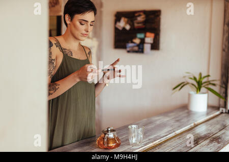 Woman taking photos of a glass teapot and an empty cup using a mobile phone for her food blog. Food blogger shooting photos for her blog at home. - Stock Photo