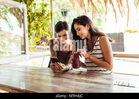 Two smiling women sitting at a restaurant looking at mobile phone. Woman showing mobile phone while another woman holds a smoothie jar in hand. - Stock Photo