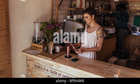 Woman standing at the billing counter of her coffee shop. Coffee shop owner operating the billing machine while a worker prepares coffee in the backgr