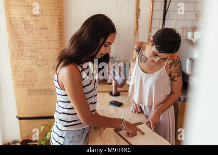 Restaurant owner helping a customer with the menu. Customer ordering food looking at the menu at the billing counter. - Stock Photo