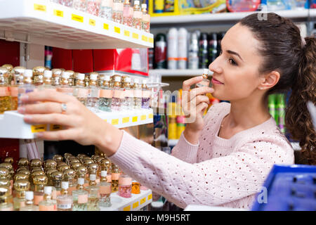 Cheerful young beautiful woman choosing fragrance on display and smiling - Stock Photo