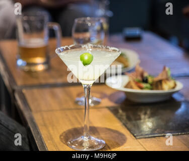 A margarita drink sits on a table in focus. In the background are a variety of alcoholic drinks including beer and wine. - Stock Photo