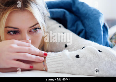 Lonely sad girl lying on bed in a bedroom - Stock Photo