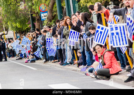 Athens, Greece. 25th Mar, 2018. People holding Greek flaks wait for the parade to start. A military parade takes place due to Independence Day in Greece. 25th March is the commemoration of the revolution of Greeks against Ottoman occupation in 25th March 1821. Credit: Kostas Pikoulas/Pacific Press/Alamy Live News - Stock Photo